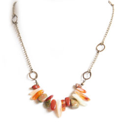 A gemstone tumble of aloe shades, on an antique brass chain, with asymmetrical brass features.